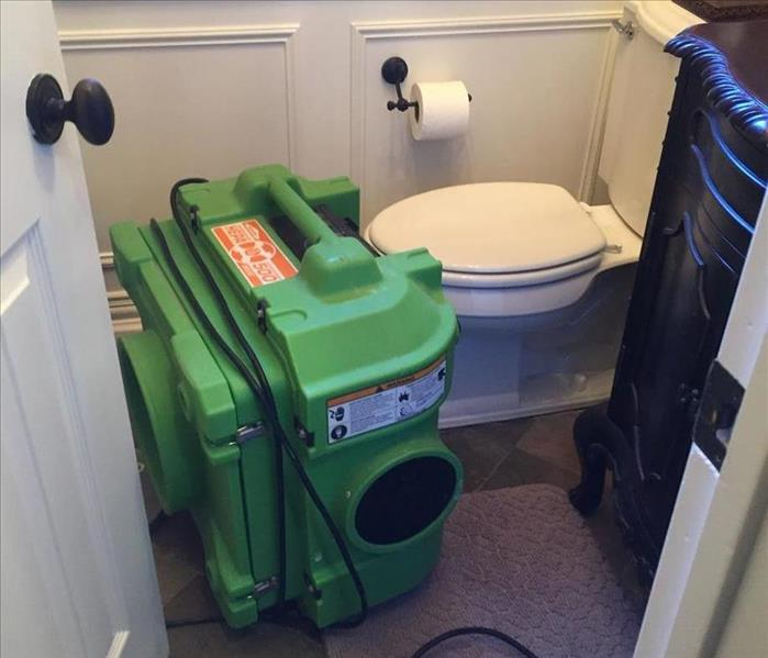 SERVPRO equipment on the floor in a bathroom.